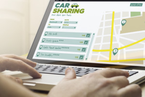 travel and trip concept: man using a laptop with car sharing software on the screen. Screen graphics are made up.